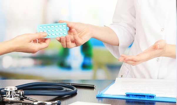 врач передает таблетки пациенту