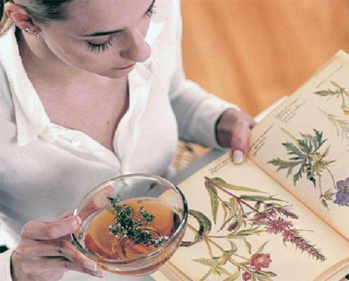 женщина пьет травяной чай и читает книгу