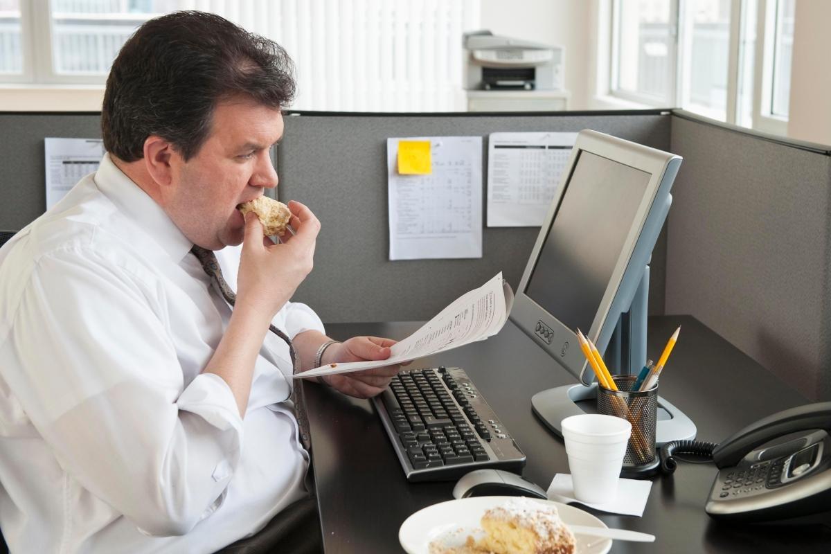 полный мужчина в офисе ест булку