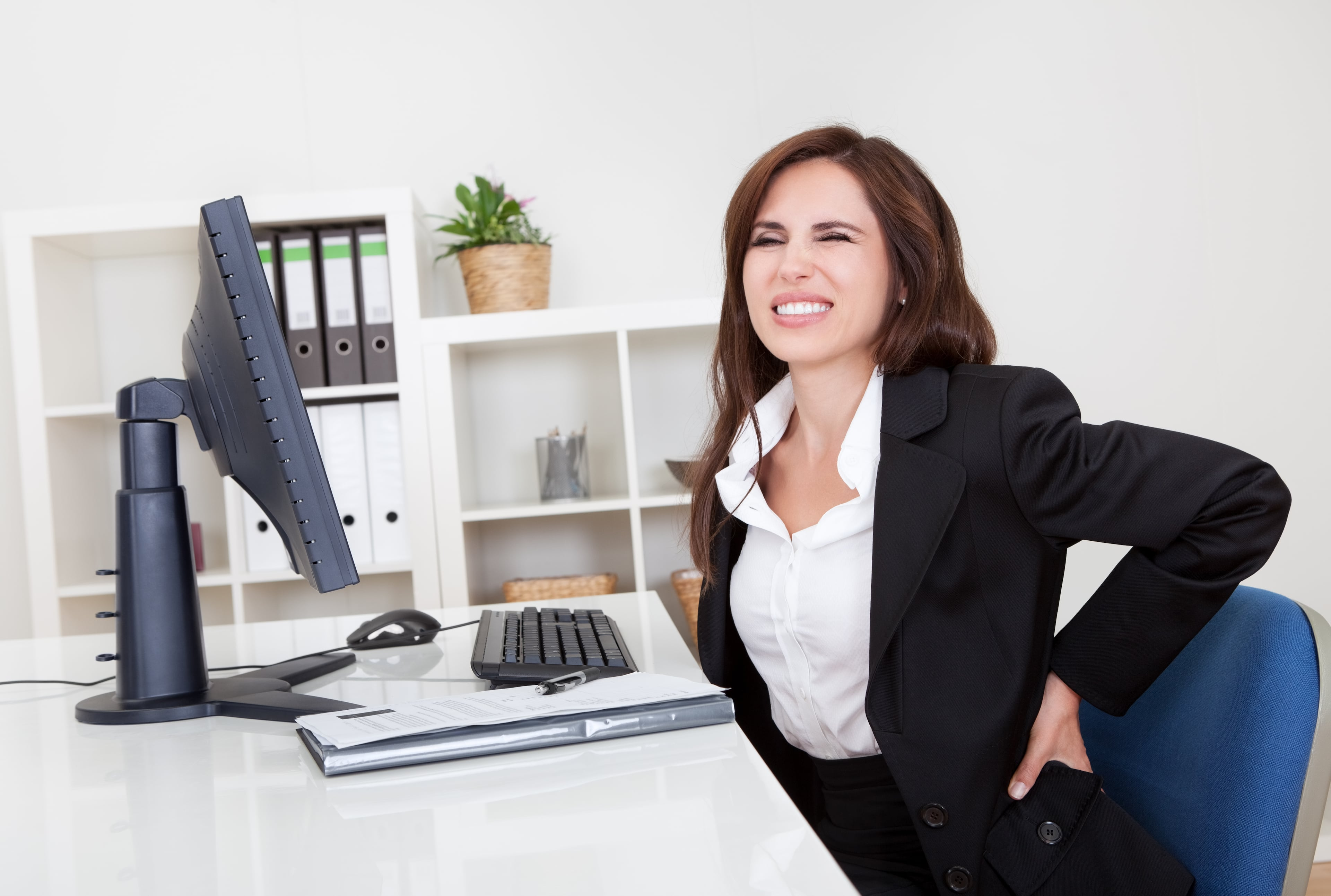 женщина в офисе держится за поясницу