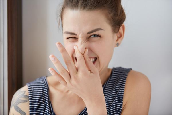 девушка зажимает нос