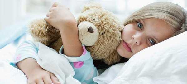 девочка лежит в кровати с мишкой